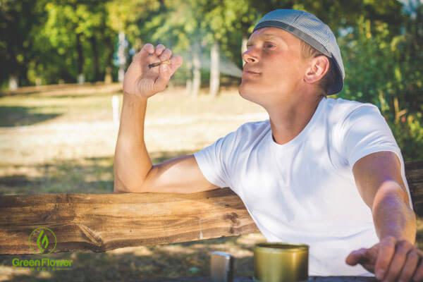 man smoking cannabis in park