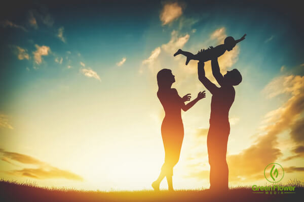 parents playing with their child during sunset