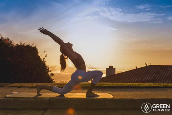 woman practicing yoga at sundown