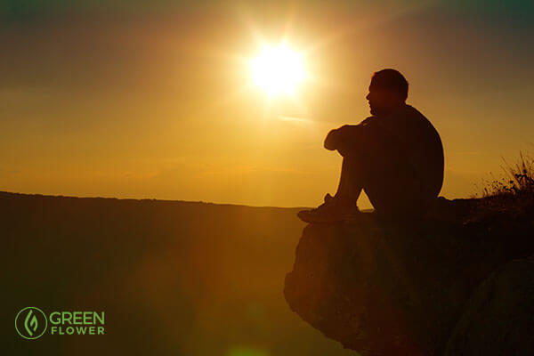 man sitting on cliff during sunset