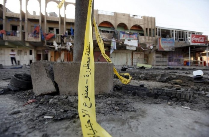 The site of a bomb attack is seen in Baghdad