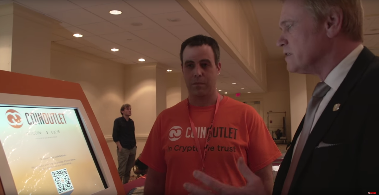 Mike Maloney deposits cash into a Bitcoin ATM created by CoinOutlet