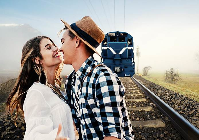 Women and man on train tracks with train approaching
