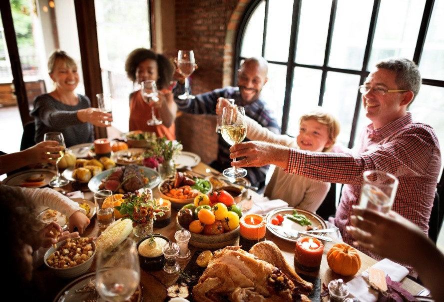 Group at holiday table - How to be a Good Thanksgiving Guest