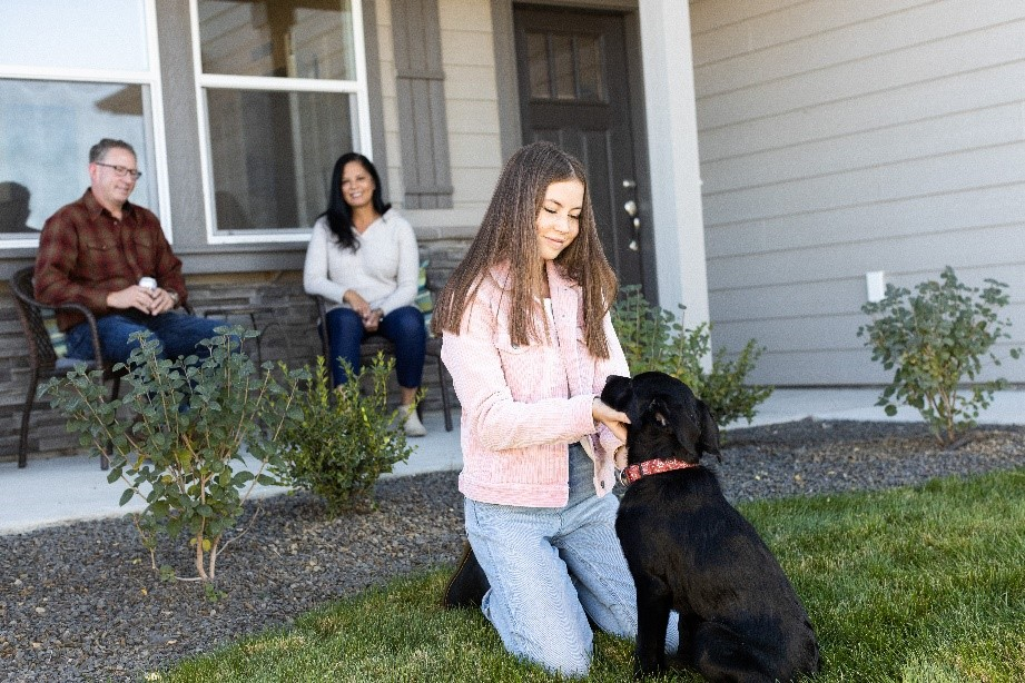 Girl petting her dog in front of their new home