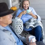 Couple enjoying their morning coffee in front of their McKenzie Meadows Village Home in Sisters, OR