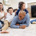 Family having fun in front of the fireplace in their new Hayden Home