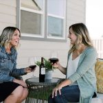 Two friends enjoying wine on the patio of a new Hayden Home