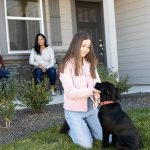 Girl with her dog and parents in front of their new Hayden Home