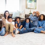 Family with mom and dad and four kids in their living room