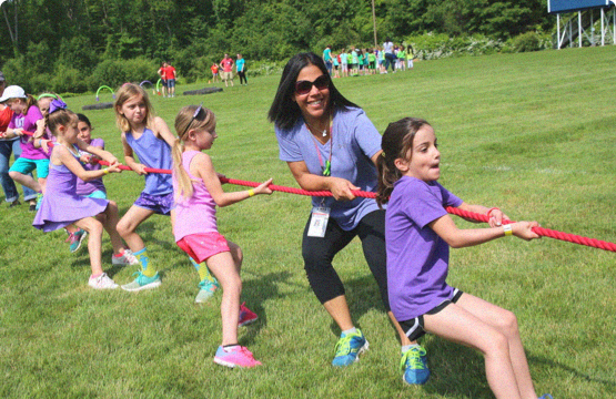 woman playing tug of war with kids outside