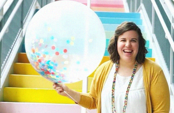 woman smiling holding a balloon