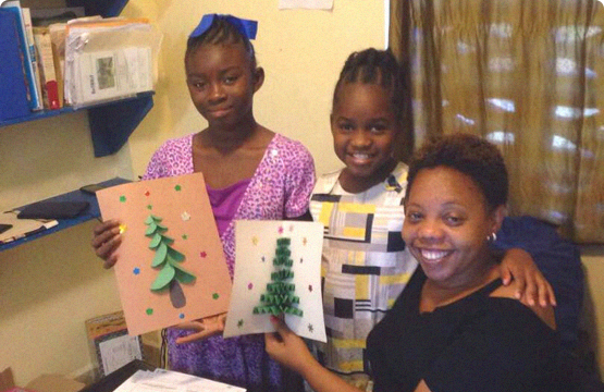 woman holding up homemade Christmas cards with two kids