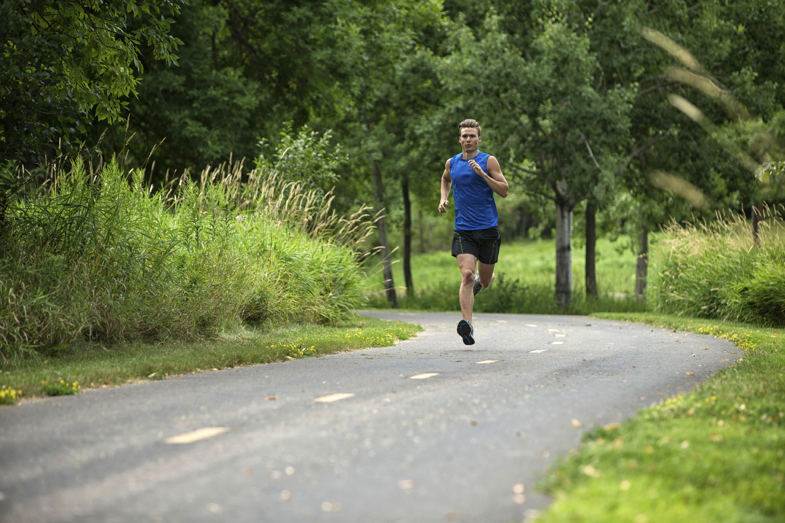 Young Male Jogger Jogging On Road