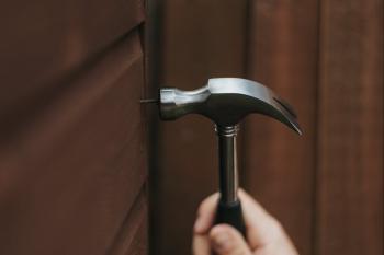 hammering a nail into a wall
