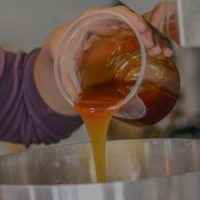 Homebrewer adds malt extract to brew kettle