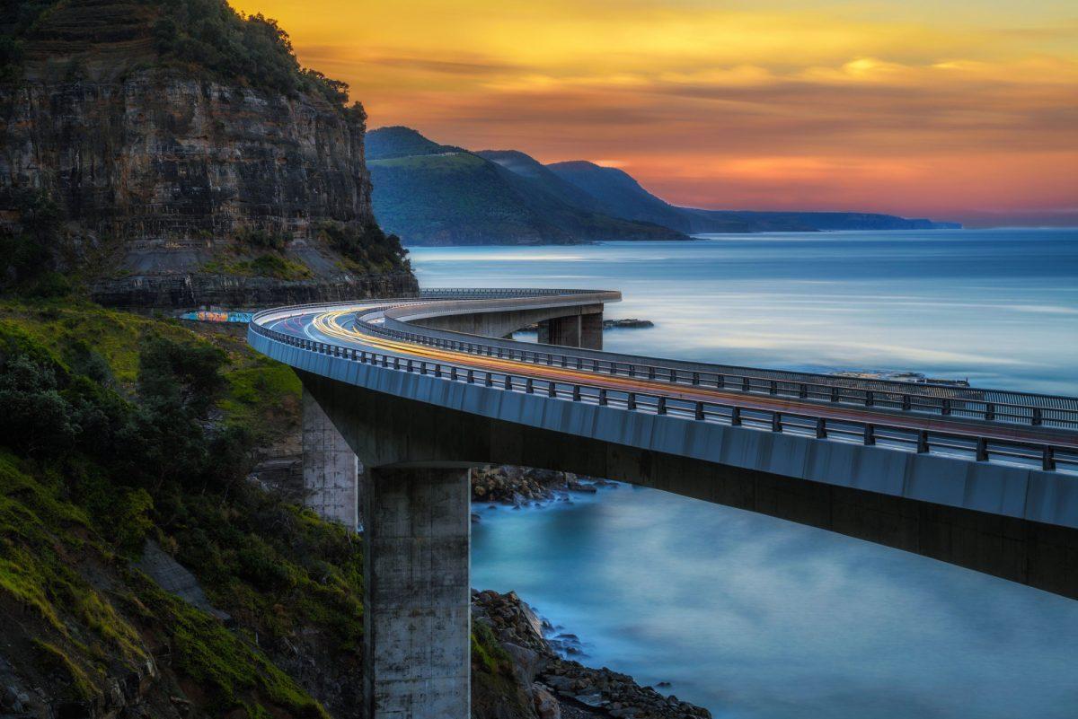 Aus Sunset over the Sea cliff bridge along Australian Pacific ocean coast nr Sydney