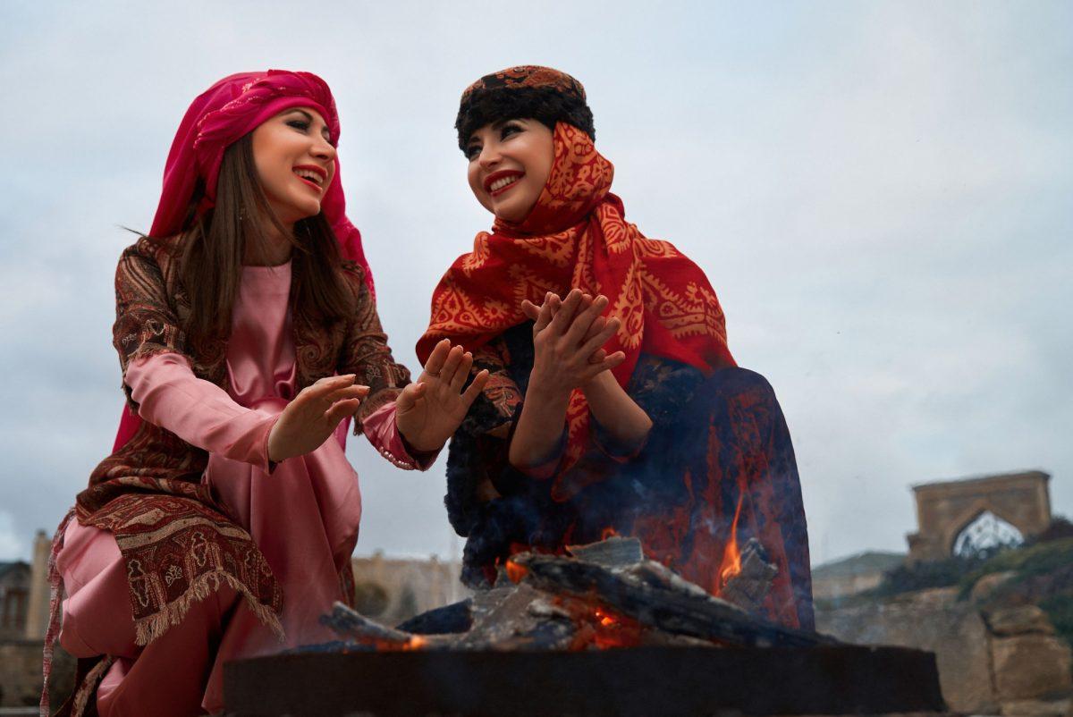 Iran Beautiful azeri women in traditional Azerbaijani dress warming hands above the bonfire