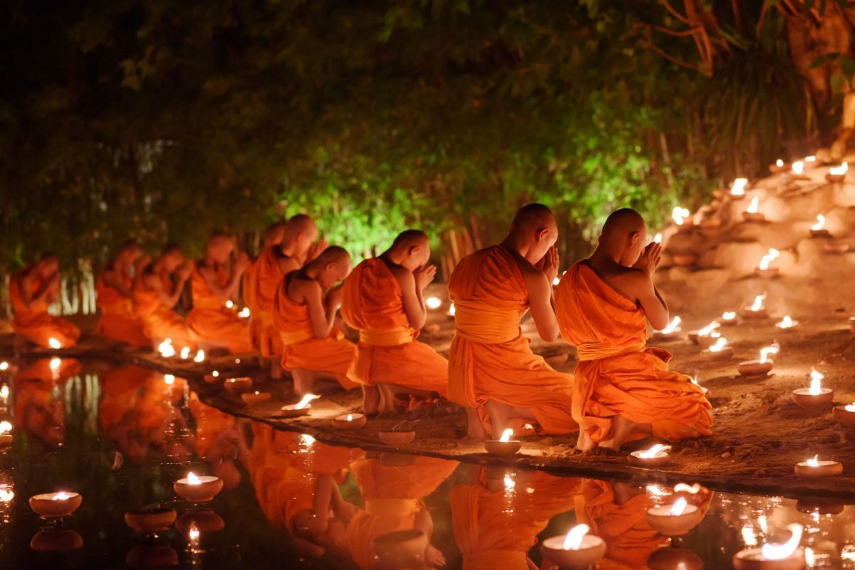 Thailand Chiang Mai monks sitting meditate with many candle in Thai temple at night