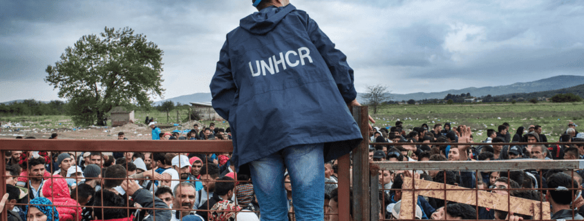A UNHCR employee talks to refugees as they wait during a rainstorm to enter inside a refugee camp near the town of Gevgelija at the Macedonian