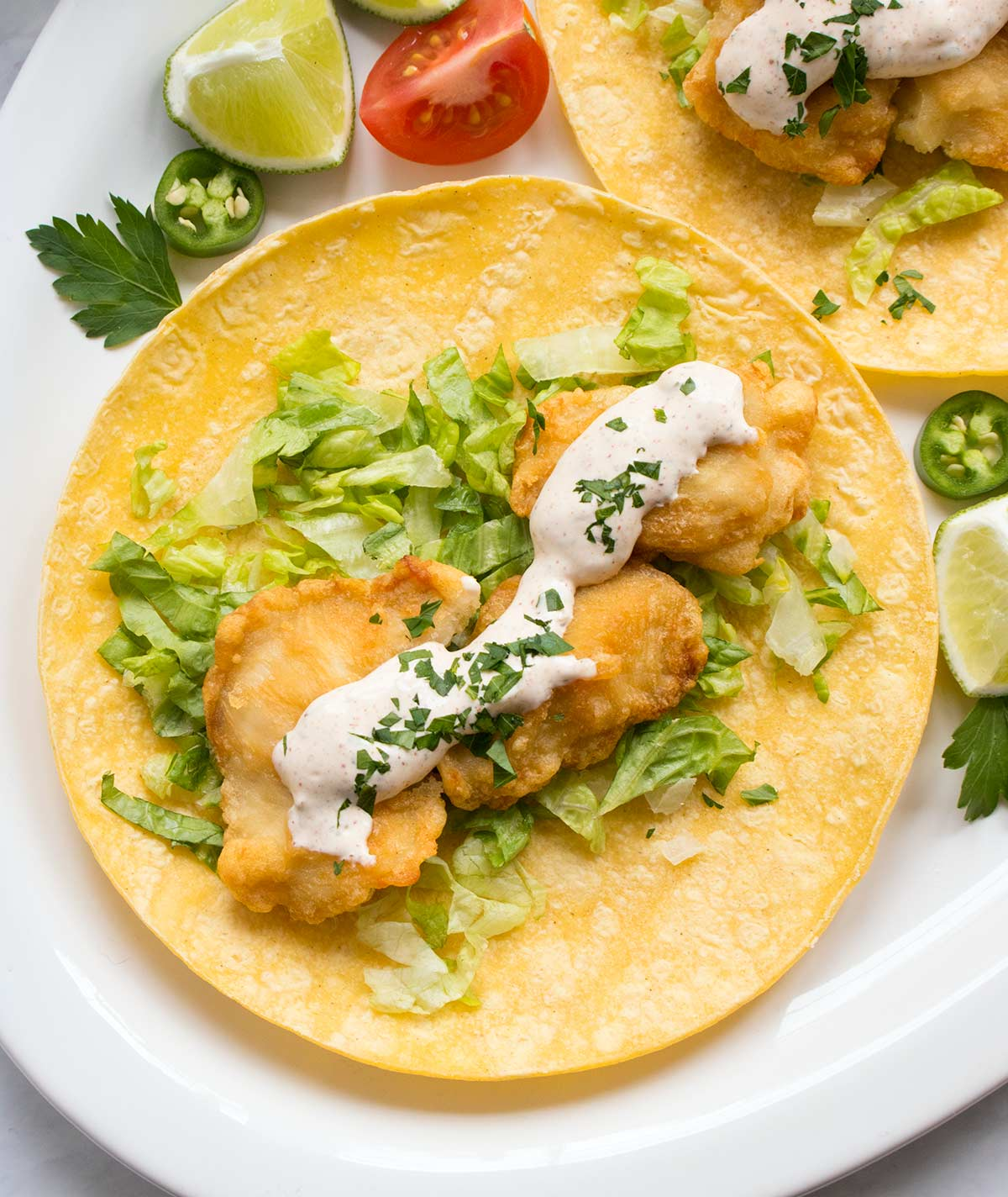 Homemade fish taco sauce on fish tacos and corn tortillas. Recipe at SoupAddict.com