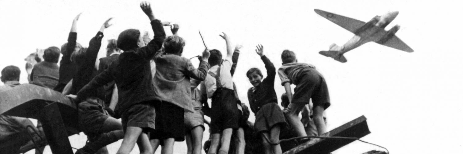 Children standing on rubble waving to plan landing at Tempelhof Airport, Berlin 1948