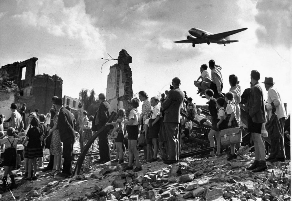 Families watch a plan landing at Berlin Tempelhof Airport During the Berlin Airlift of 1947-48