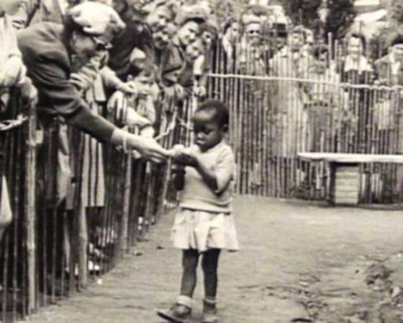 "At a ""Peoples Shows"" in Brussels, Belgium, where a young Black girl is fed by spectators. Image: Public Domain"
