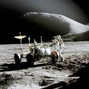 "Astronaut James B. Irwin, works at the Lunar Roving Vehicle at the Hadley-Apennine landing site. The shadow of the Lunar Module ""Falcon"" is in the foreground. This view is looking northeast with Mount Hadley in the background. This photograph was taken by Astronaut David R. Scott on the 31st of July, 1971."