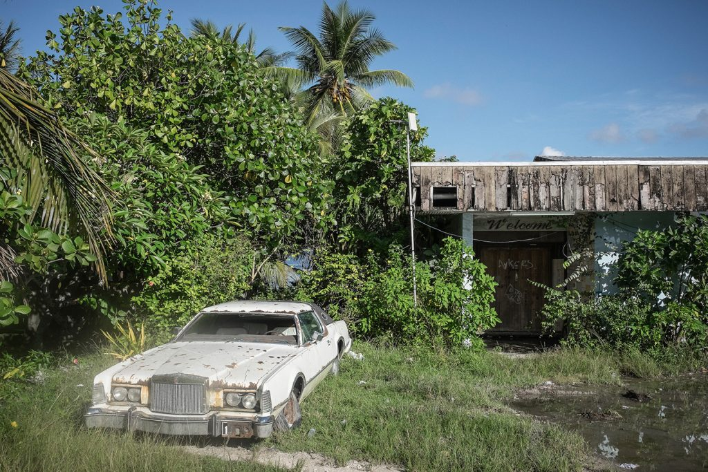 An abandoned vehicle stands by the side of a road. Many cars have been abandoned along Nauru's roads and in backyards. With an unemployment rate of around 90%, much of the population is dependent on government handouts which are becoming increasingly unaffordable with the sharp reduction in phosphate output on the island. Image by Vlad Sokhin