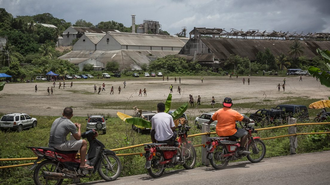 People watch an Australian rules football game in front of the Phosphate processing factory. The sport is very popular in Nauru and, along with weightlifting, is the national sport of the island nation. Image by Vlad Sokhin