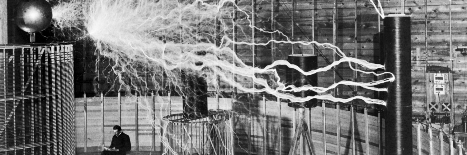 """Photograph of Serbian-American inventor Nikola Tesla in his laboratory in Colorado Springs around 1899, supposedly sitting reading next to his giant """"magnifying transmitter"""" high voltage generator while the machine produced huge bolts of electricity."""