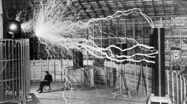 "Photograph of Serbian-American inventor Nikola Tesla in his laboratory in Colorado Springs around 1899, supposedly sitting reading next to his giant ""magnifying transmitter"" high voltage generator while the machine produced huge bolts of electricity."