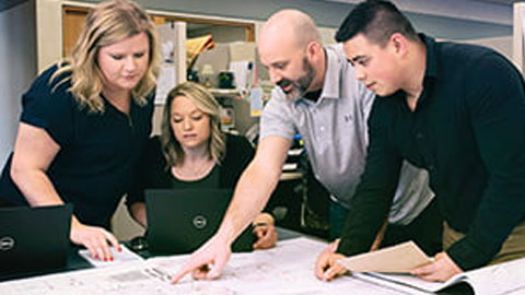 Four individuals looking at engineering drawings