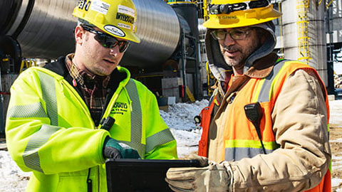 Electrical construction workers looking at a tablet on a jobsite