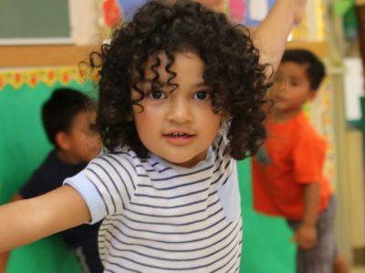 Preschool girl dancing looks at you