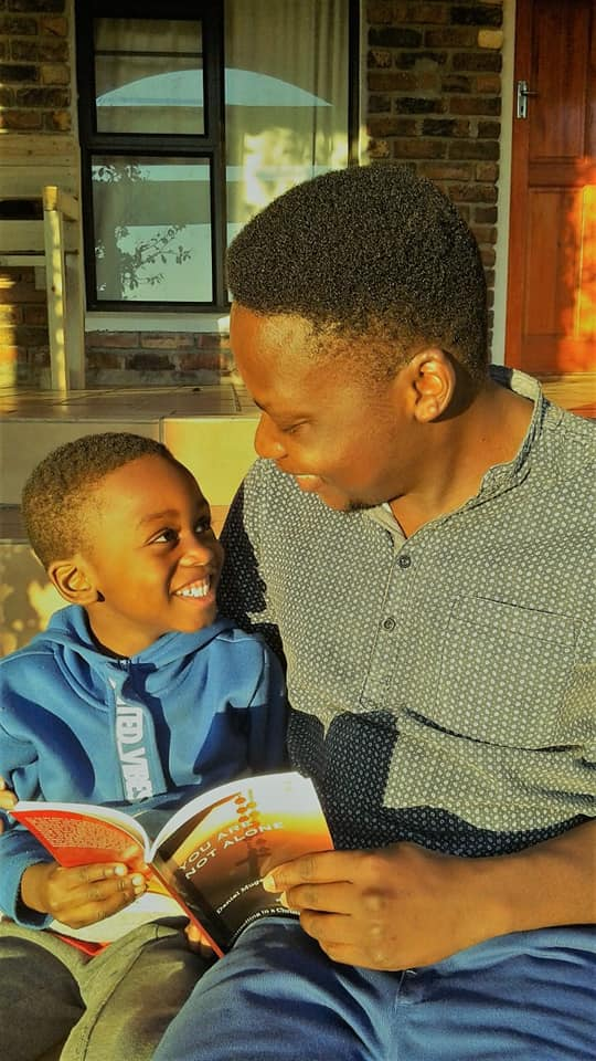 Happiness with book You Are Not Alone by Daniel Mugaviri in South Africa