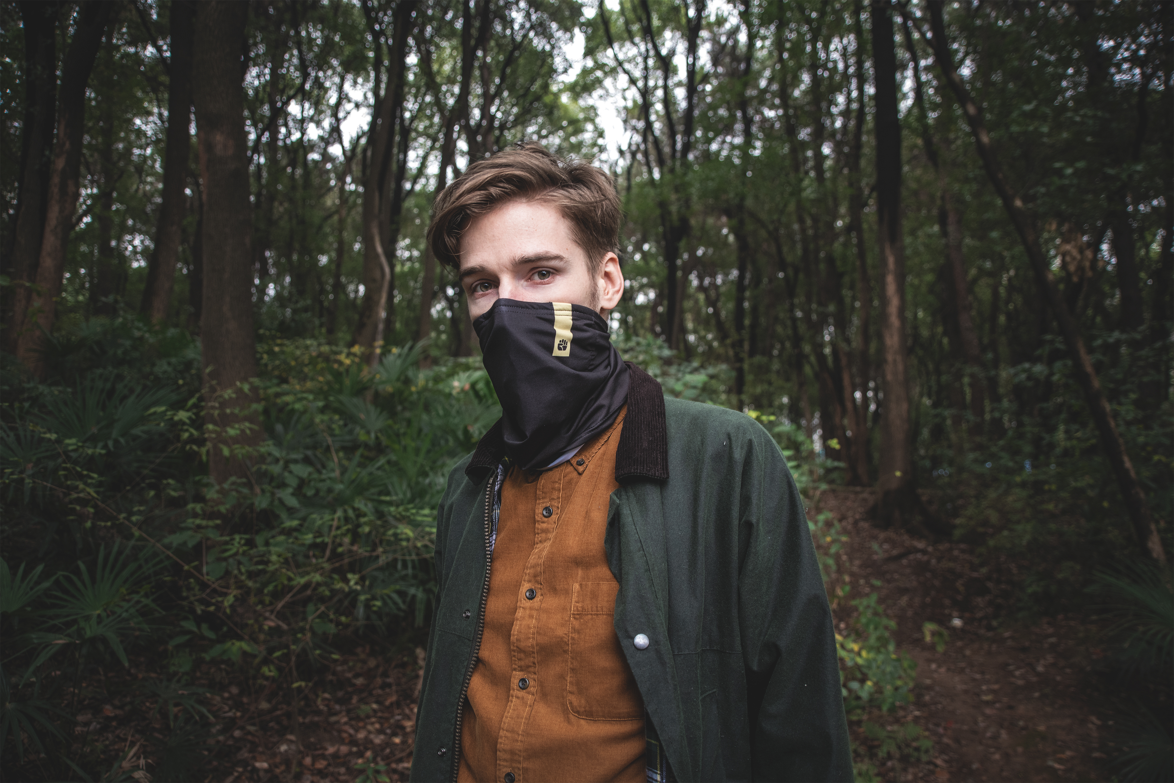 Male wearing scarf hiking in the woods