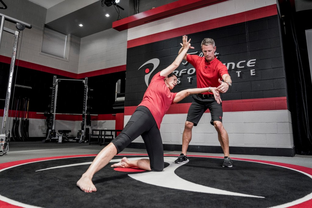 Dan Hellman and Janet Alexander demonstrate an ELDOA stretch at the PGA Teaching and Coaching Summit January 21