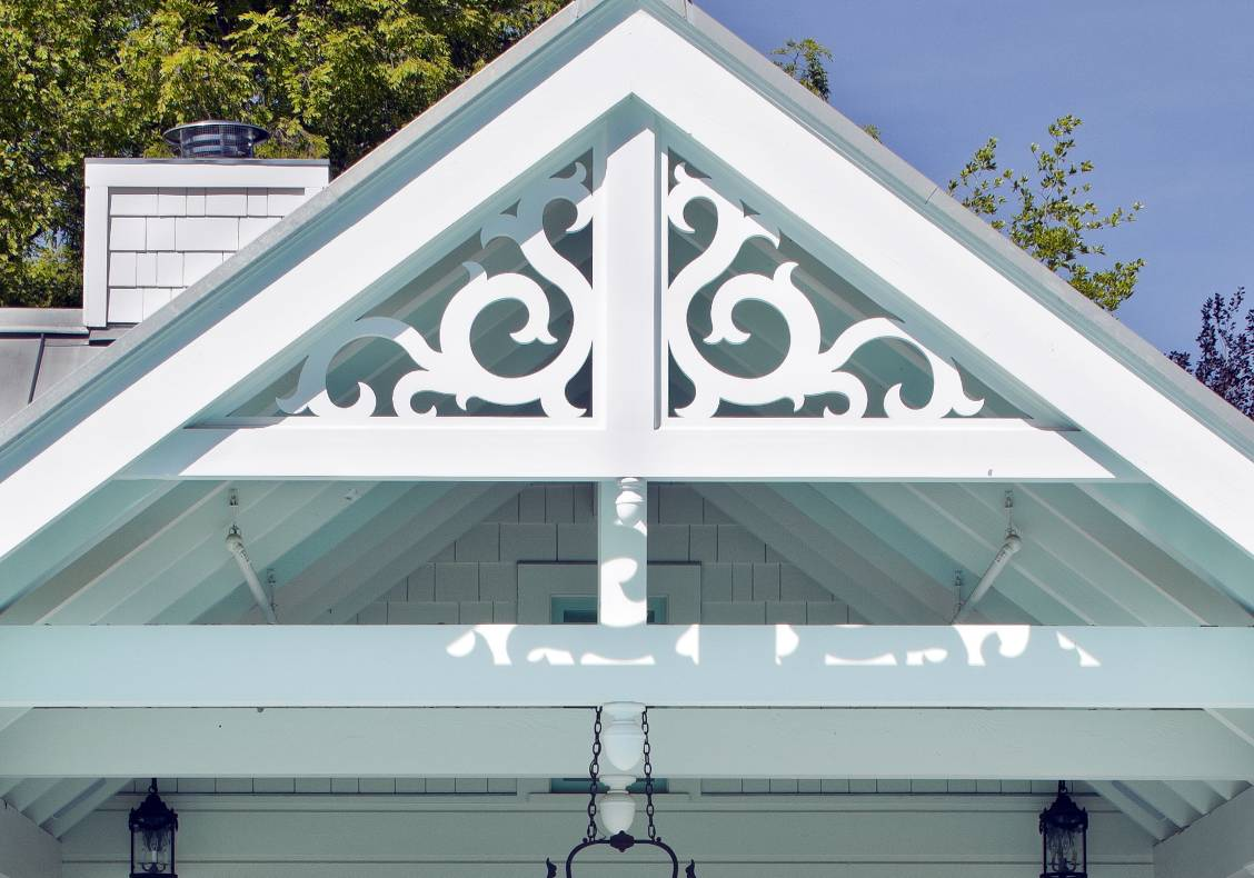 Water jet cut victorian scroll gable ornamentation gives a playful, cheerful frame to the covered dining porch overlooking the pool.