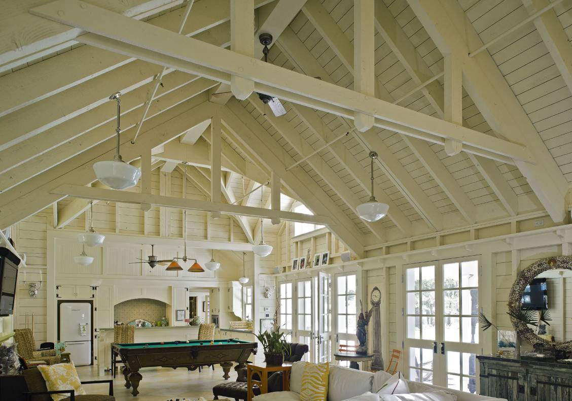 Clerestory windows, multiple french doors, whitewashed open truss ceiling, and schoolhouse lights evoke a vacation home at the beach.