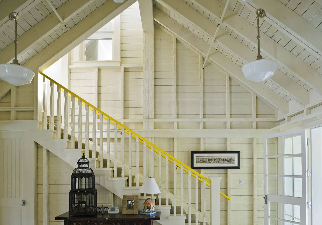 Open stud framing whitewashed with bright yellow railing and interior window to guest bedroom.