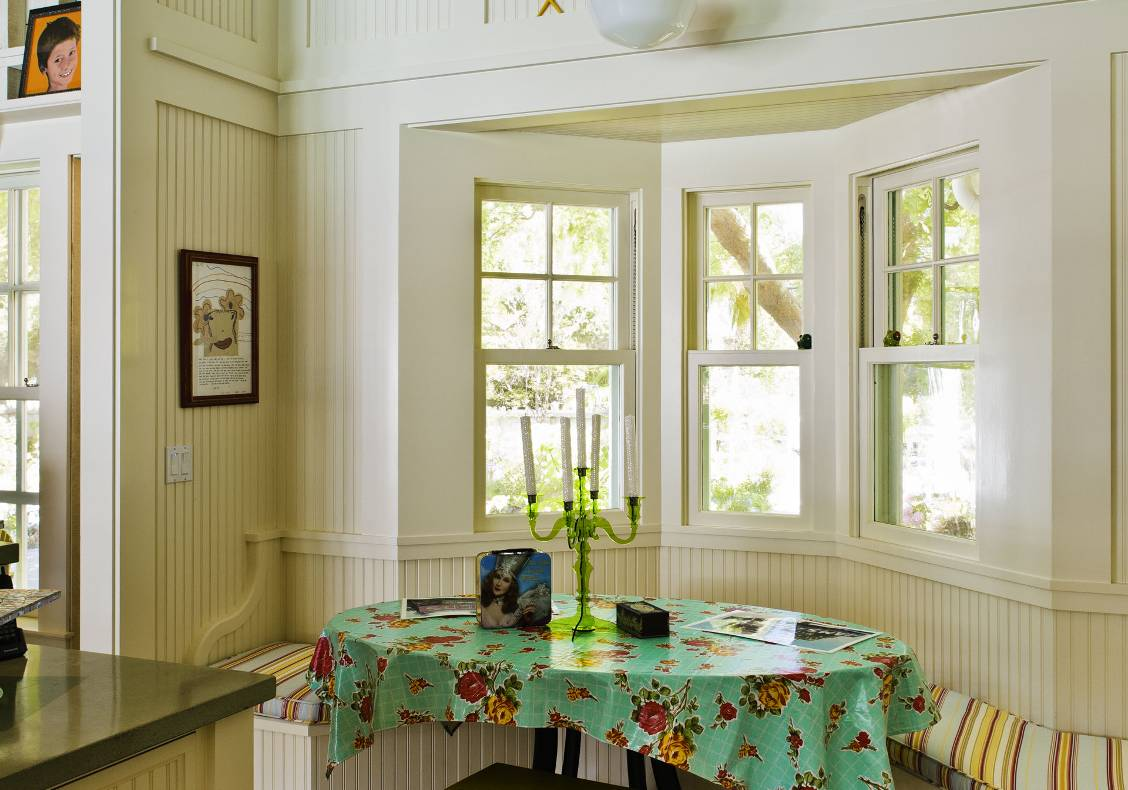 Custom double hung windows frame views at this cozy bay in the kitchen with built-in bench seating and seaside accents.