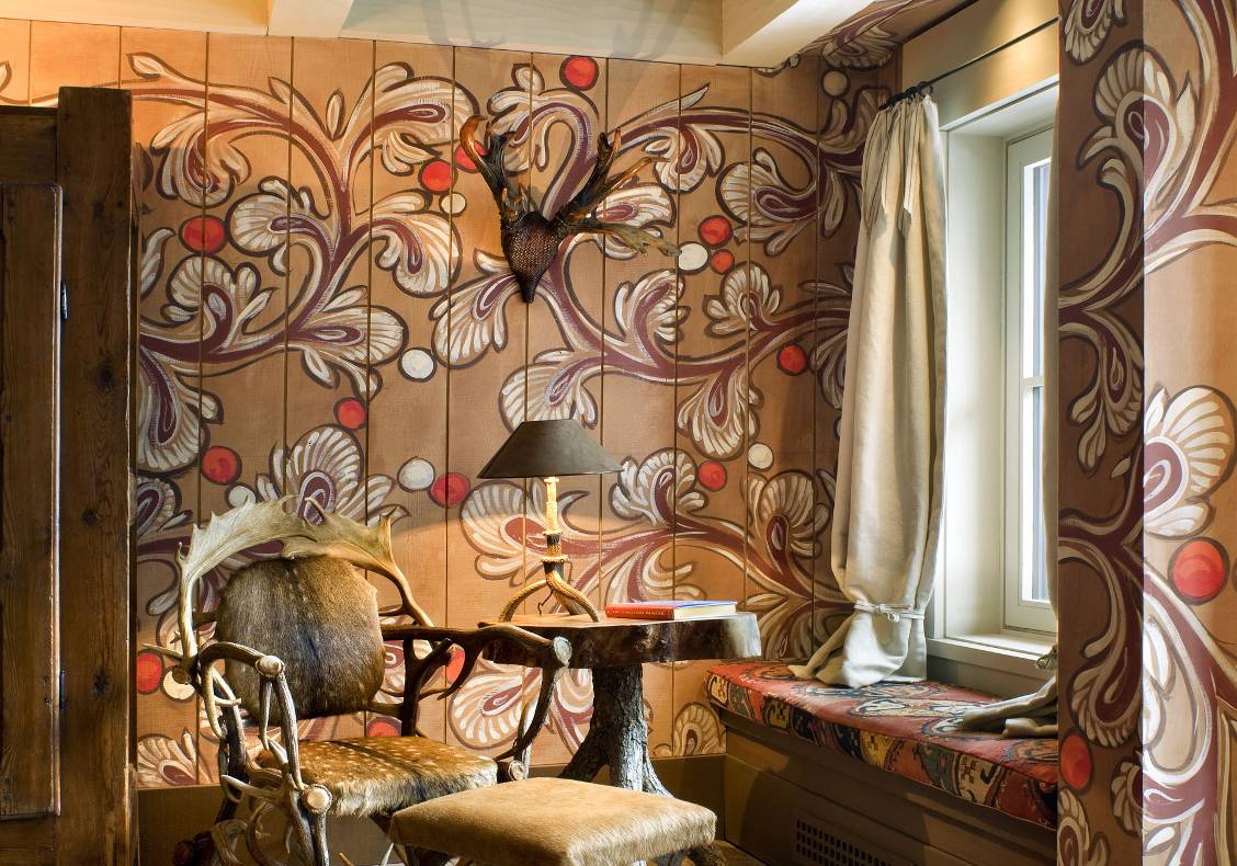 Master bedroom with window seat, paisley-painted walls, and antique antler furnishings.