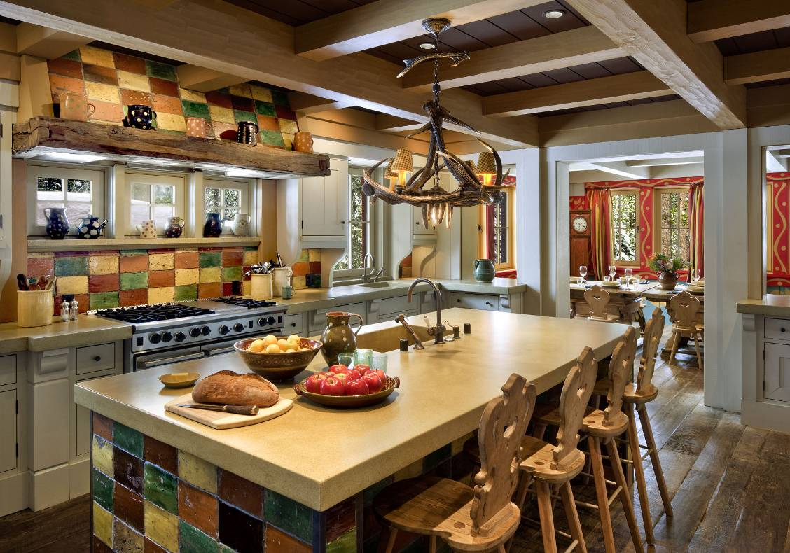 View of kitchen with reclaimed 18th century tiles, concrete counter, Swiss wooden stools.