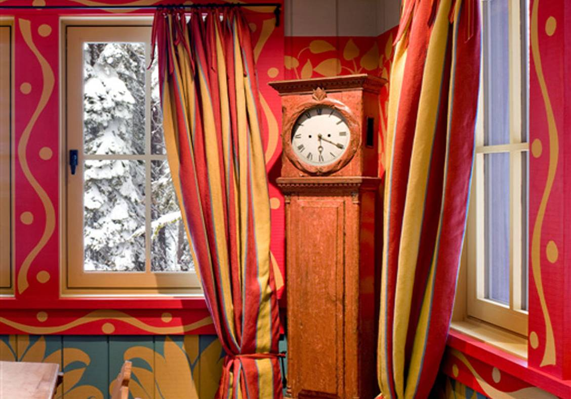 Dining room with whimsical walls, curtains, and grandfather clock.