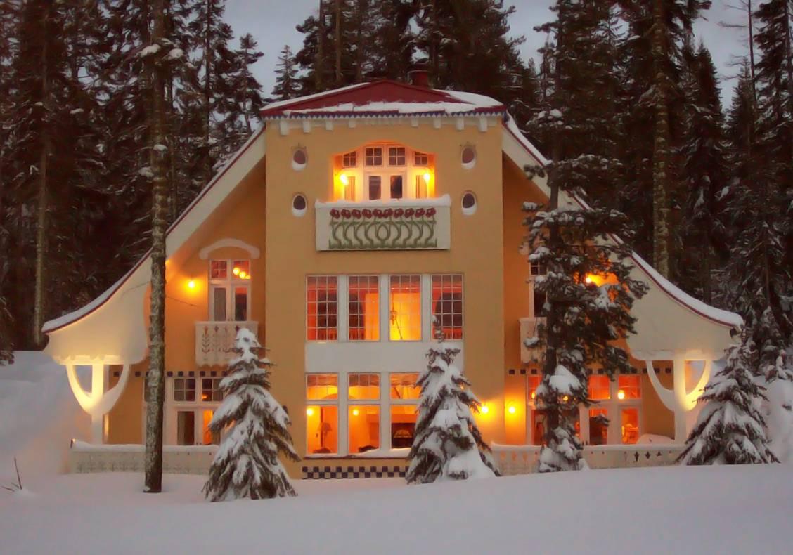 Exterior of this mountain home glows through the fresh evening snowfall