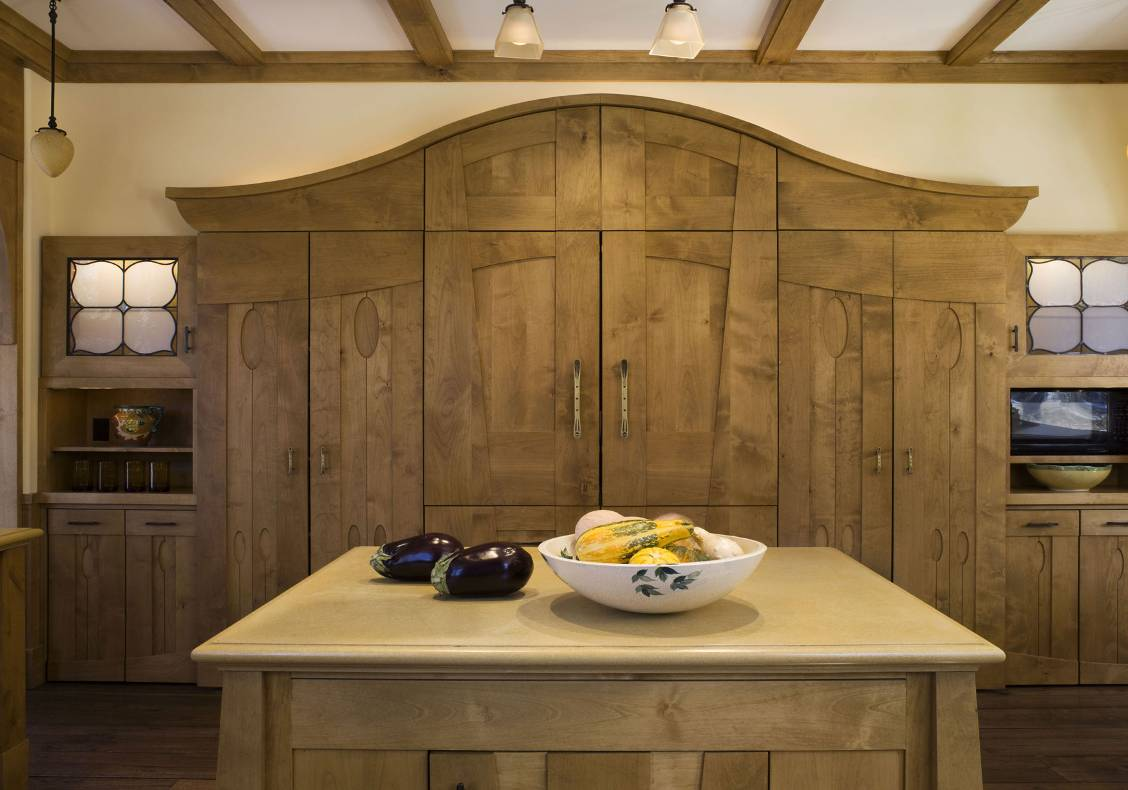 A stained island with carved cut outs and butcher block countertop offsets the richly painted kitchen cabinets.