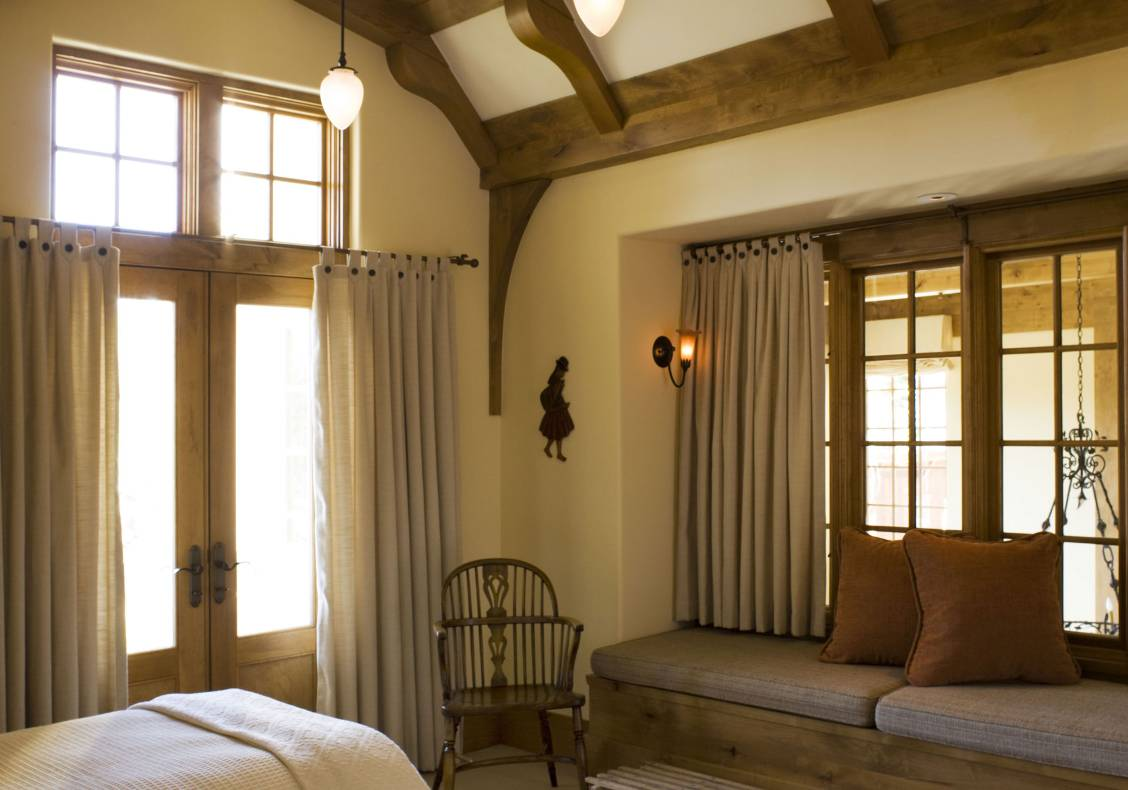 Exposed timber beams articulate the ceiling of a bedroom with an interior window seat that opens to the central space.