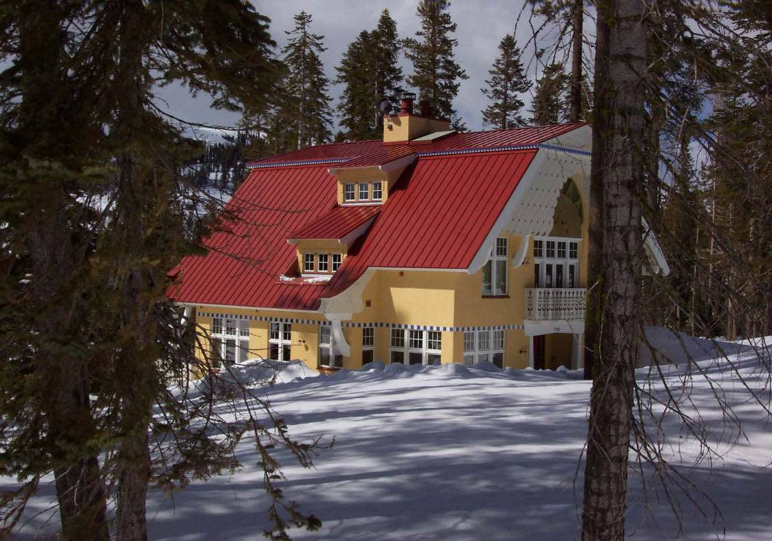 Gambrel or double sloping roof shield the exterior of this home from snow.  Stepping dormer windows provide views from the stair at the upper levels of this cheerful home.
